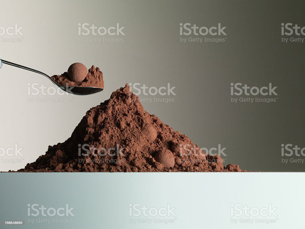 Spoon over heap of cocoa powder stock photo