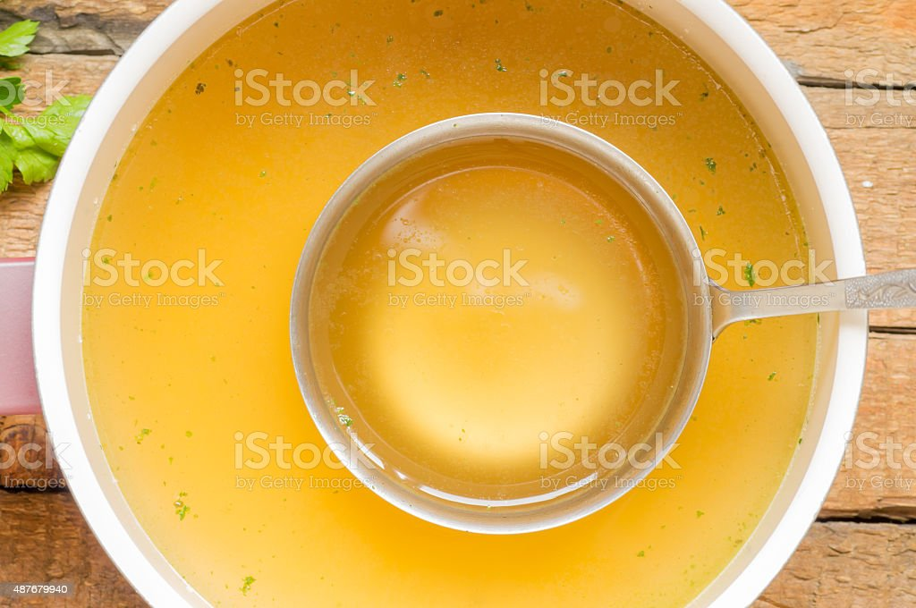 Spoon with bouillon to the pan with bouillon background stock photo