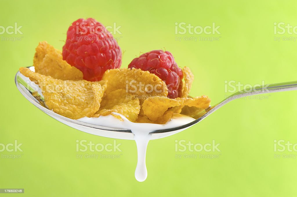 spoon with corn flakes and raspberry on green background royalty-free stock photo