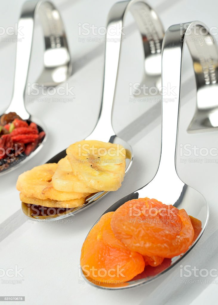 Spoon with dried fruits on table stock photo
