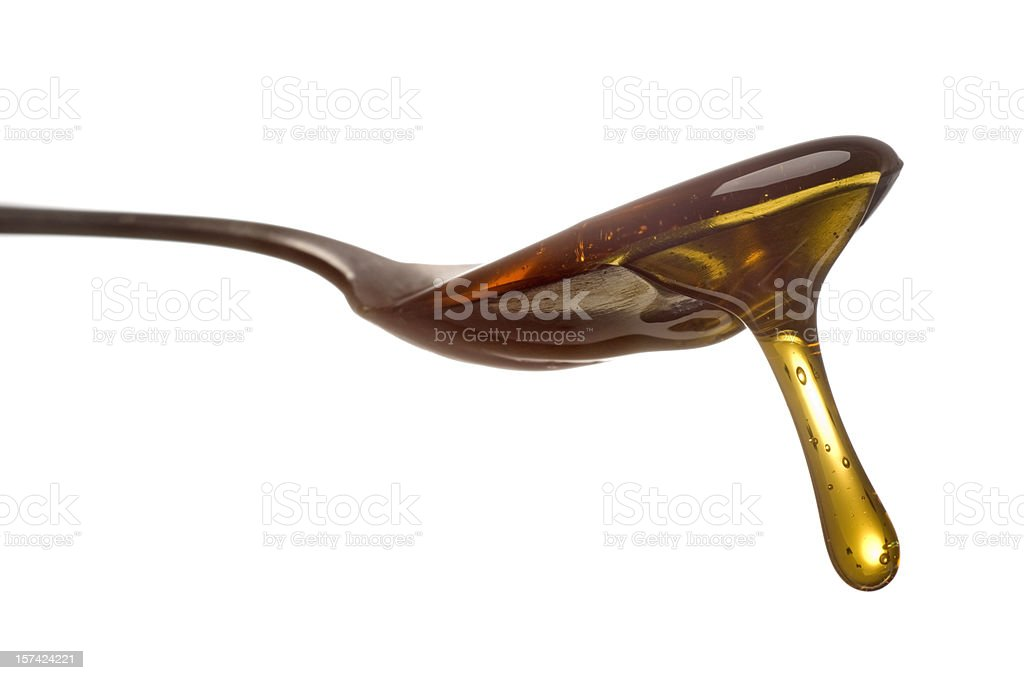 Spoon with dripping sirup or honey close-up royalty-free stock photo