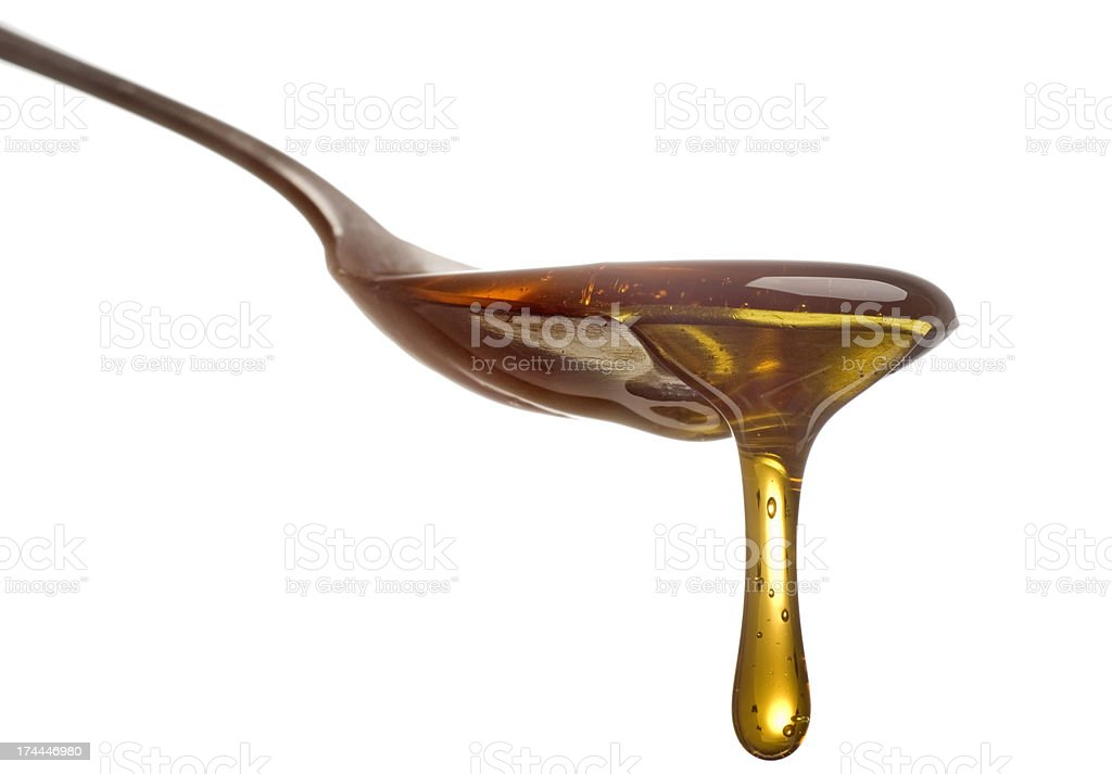 Spoon with dripping sirup or honey close-up stock photo