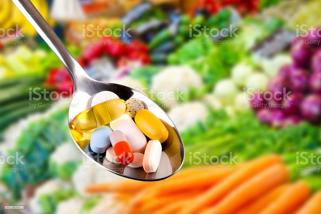 spoon with pills, dietary supplements on vegetables background stock photo
