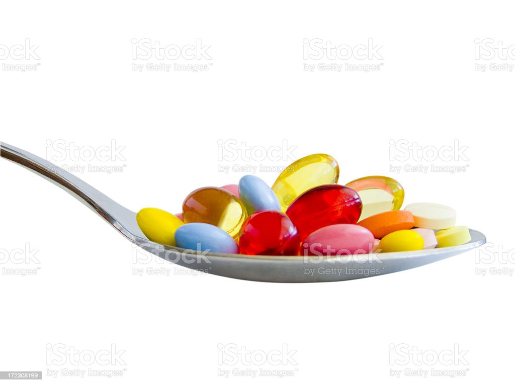 Spoonful of medicine pills and capsules stock photo