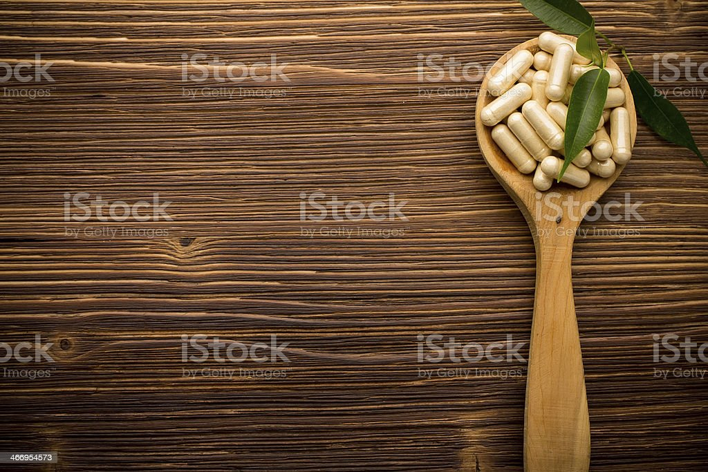 A spoonful of pills against a wood background  stock photo