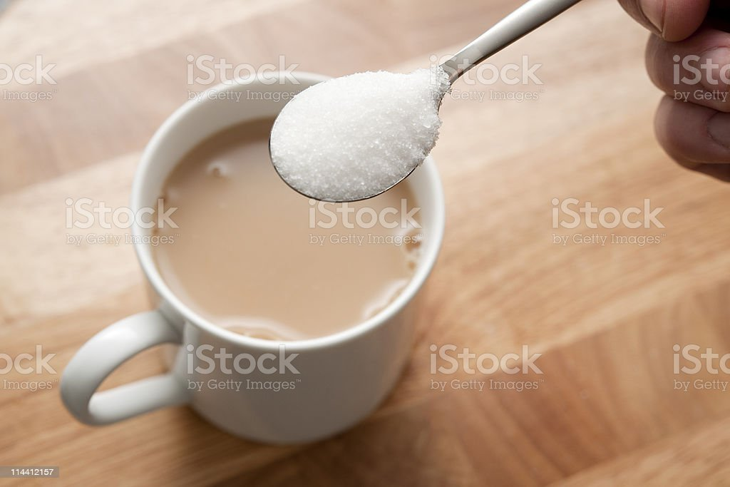 spoonful with sugar over mug of tea stock photo