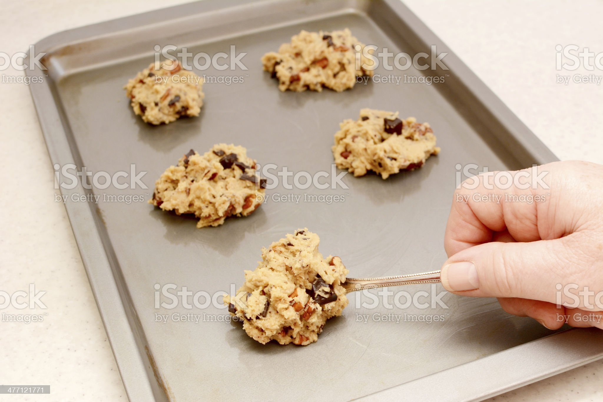 Spooning chocolate chip and pecan cookie dough royalty-free stock photo