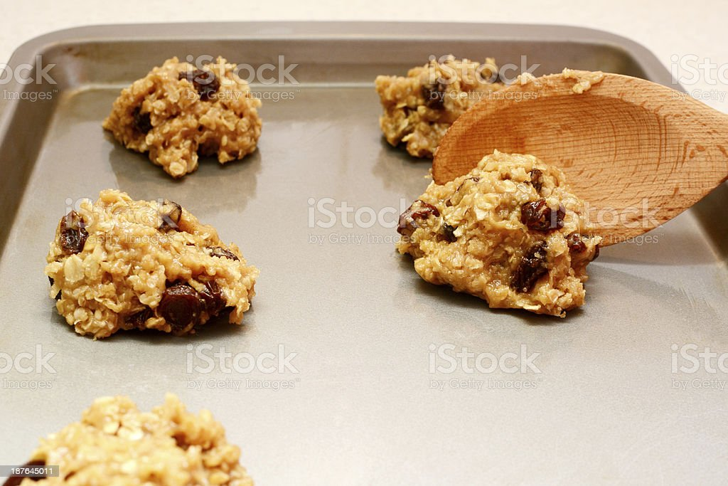 Spooning oatmeal raisin cookie dough onto a baking sheet stock photo