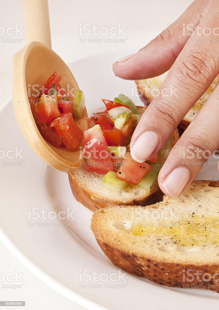 Spooning Tomatoes on Crostini Close-up royalty-free stock photo