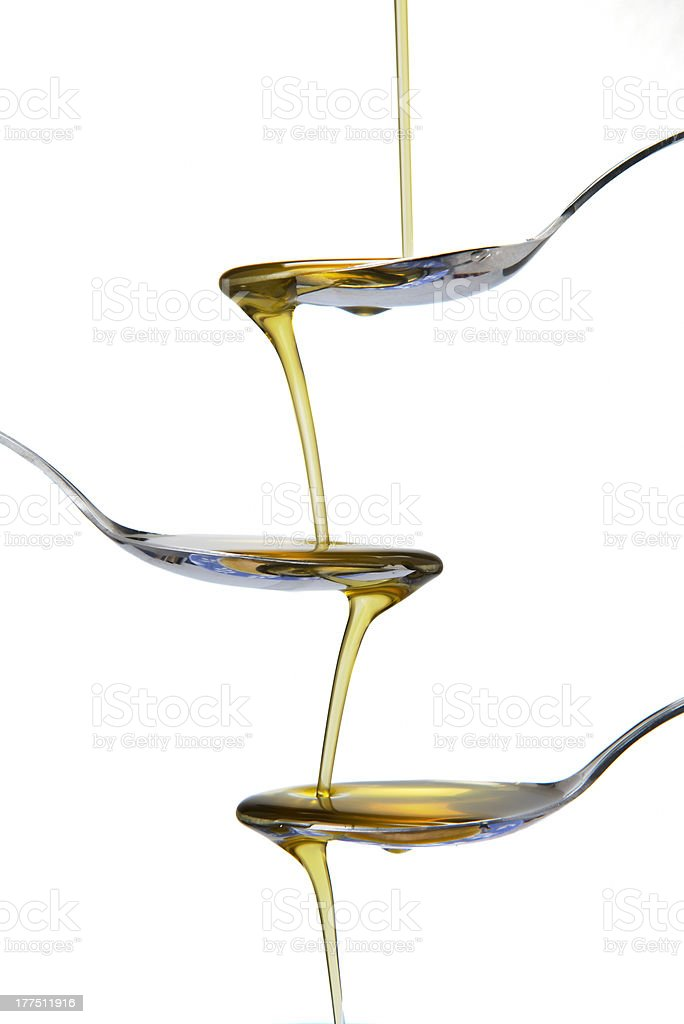 Spoons and olive oil falling royalty-free stock photo