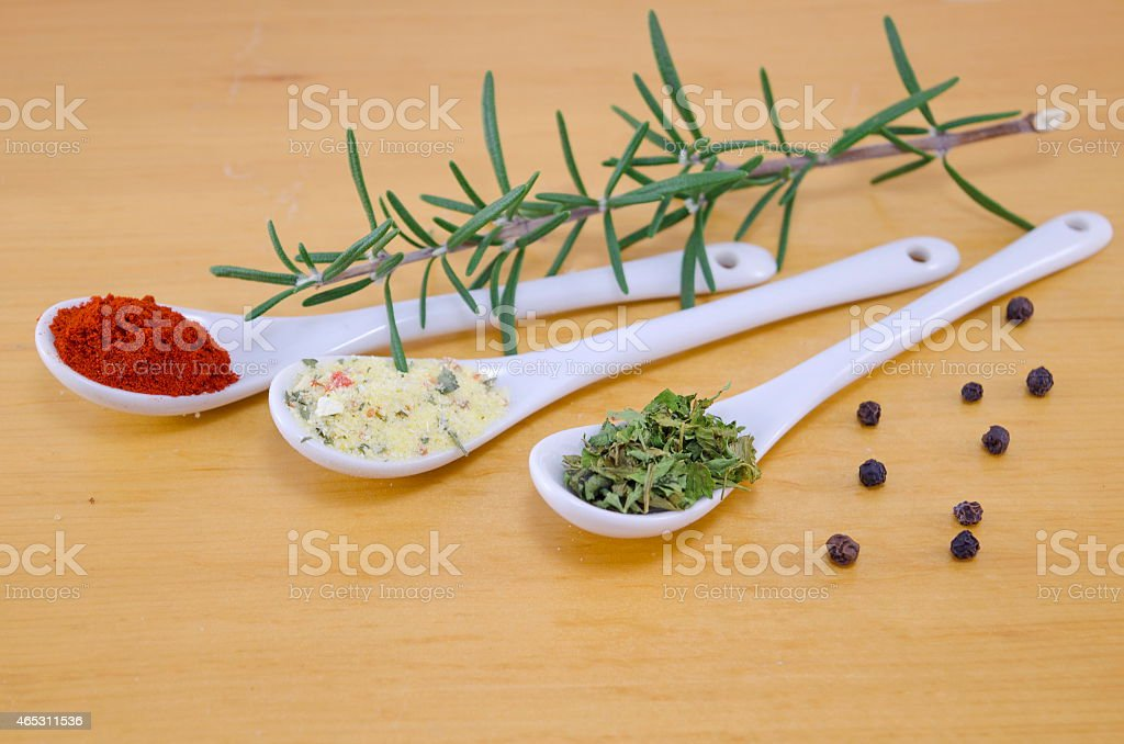 Spoons filled with spices on a wooden background royalty-free stock photo