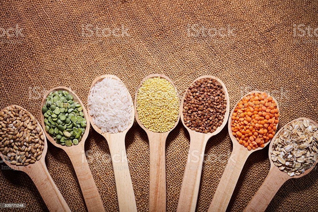 Spoons with groats on sacking stock photo
