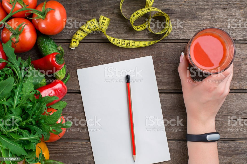 Sport and diet. Vegetables, a glass of tomato juice and centimeter. Peppers, tomatoes, salad on rustic background stock photo