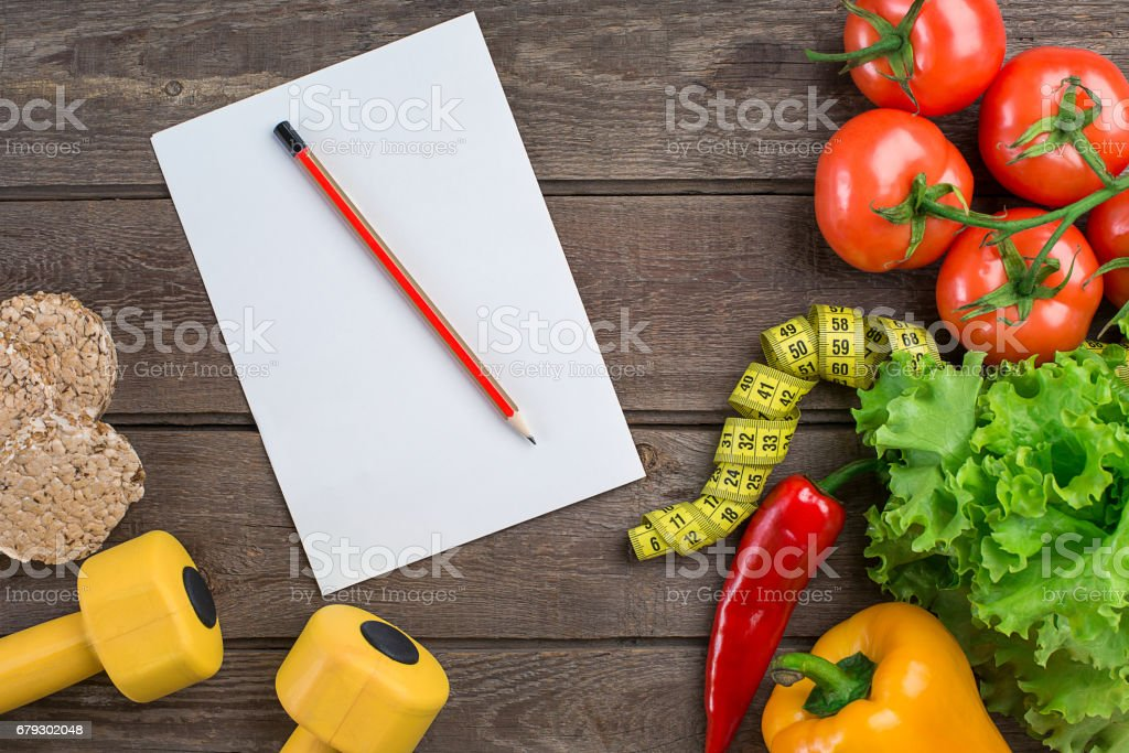 Sport and diet. Vegetables, dumbbells and centimeter. Peppers, tomatoes, salad on rustic background stock photo
