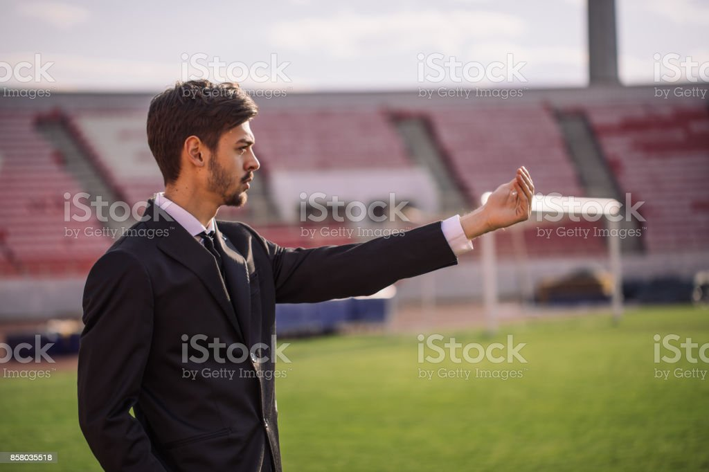 One man, young and handsome, soccer manager on the soccer field,...