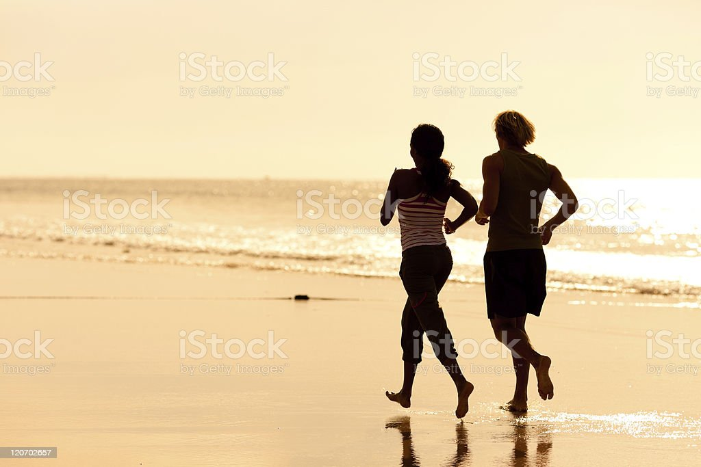 Sport couple jogging on the beach royalty-free stock photo
