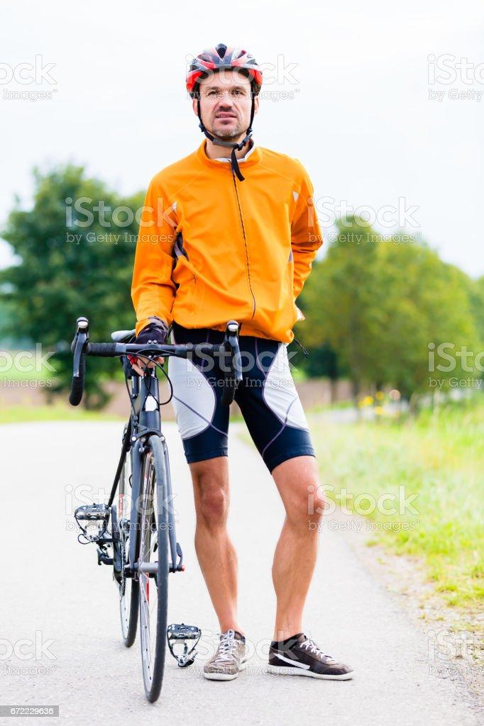 Sport Cyclist with bike having break stock photo