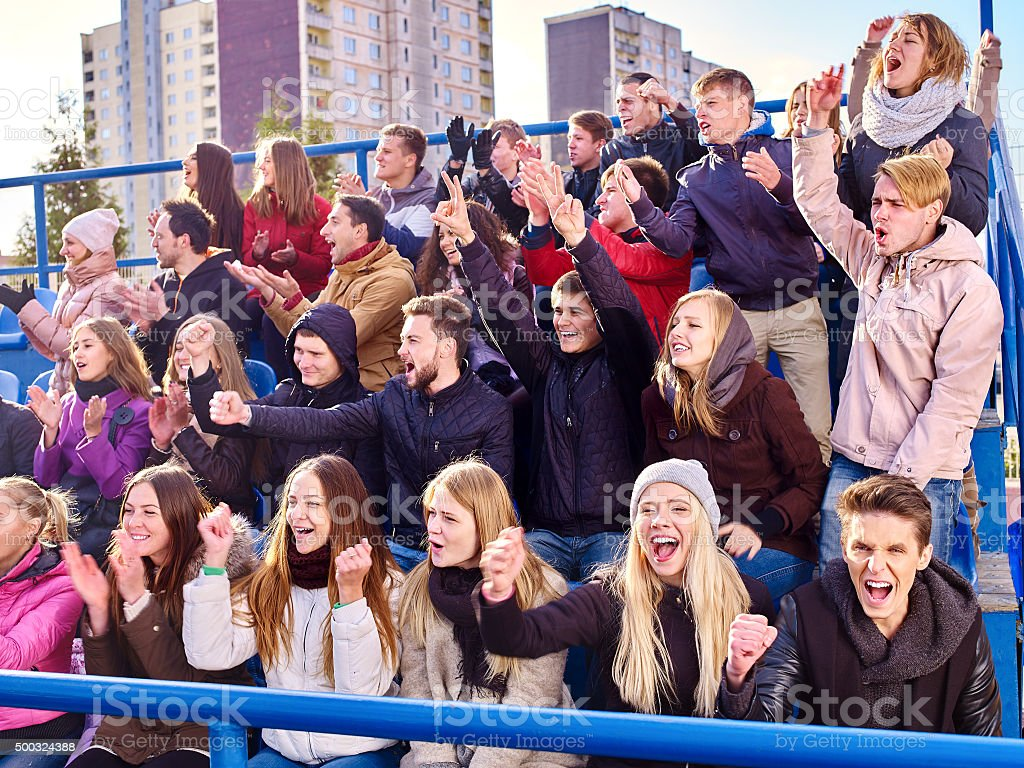 Sport fans clapping and singing on tribunes stock photo