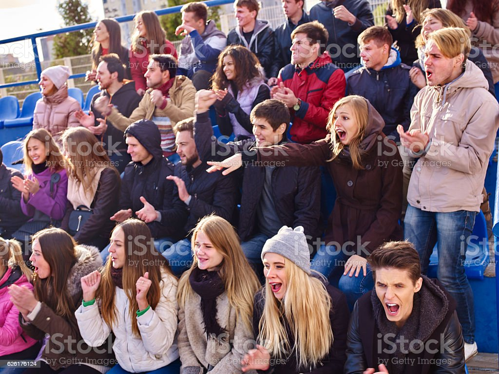 Sport fans clapping and singing on tribunes. stock photo