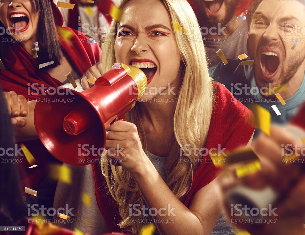 Sport fans: Girl is shouting in megaphone stock photo