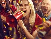 Sport fans: Girl is shouting in megaphone