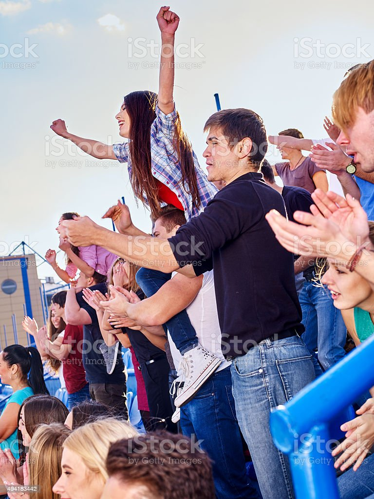 Sport fans hands up and singing  on tribunes stock photo