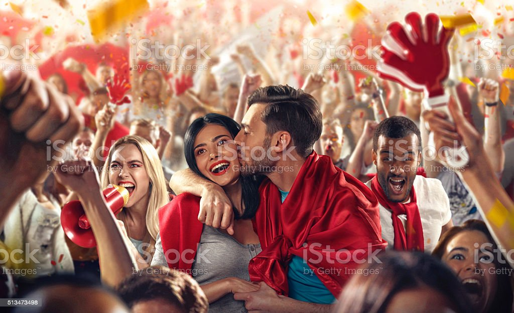 On the foreground a group of cheering fans watch a sport championship...