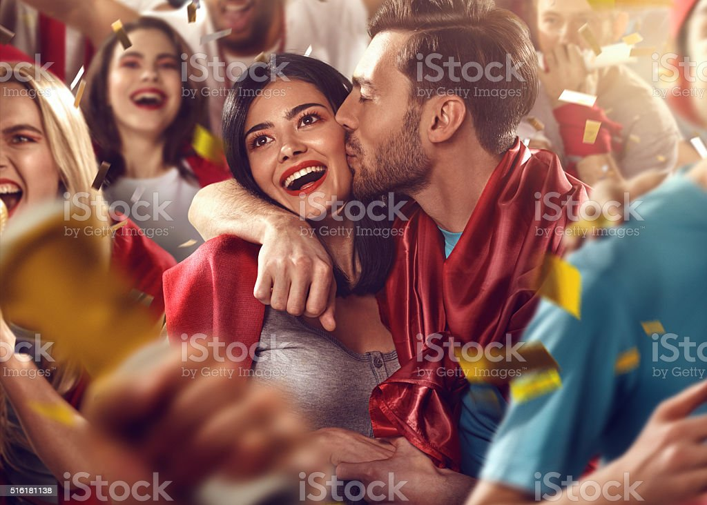 Sport fans: Man kisses woman stock photo