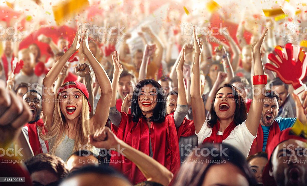 Sport fans: Three girls put hands in the air stock photo