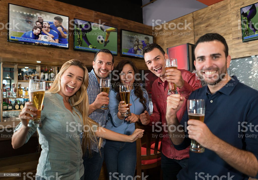 Sport fans watching a football game at the pub stock photo
