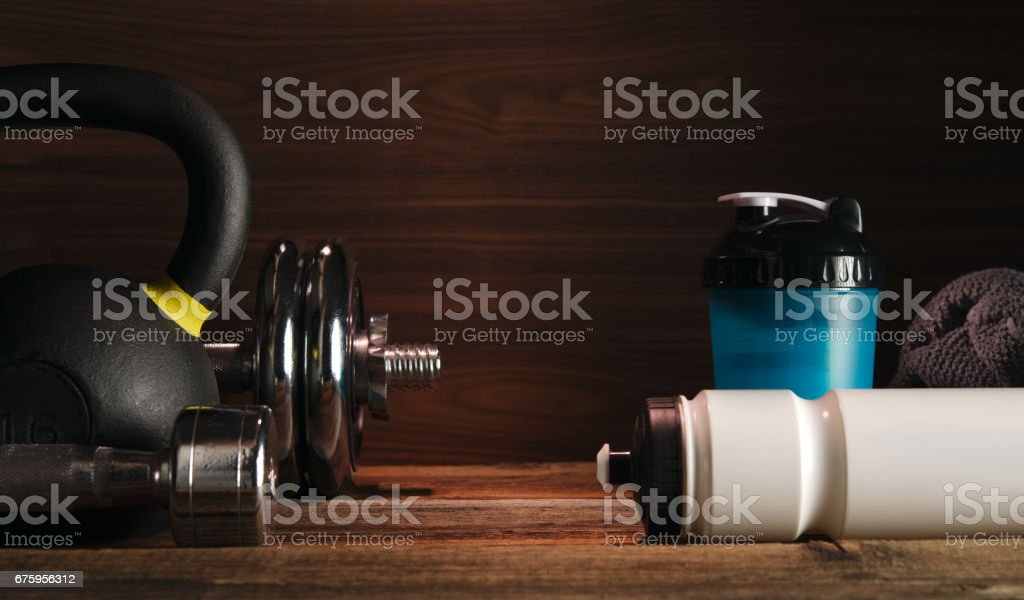 Sport fitness bodybuilding healthy lifestyle and weightlifting concept Grey towel Protein shake bottle Two Dumbbells with plates on wooden floor Gym background stock photo