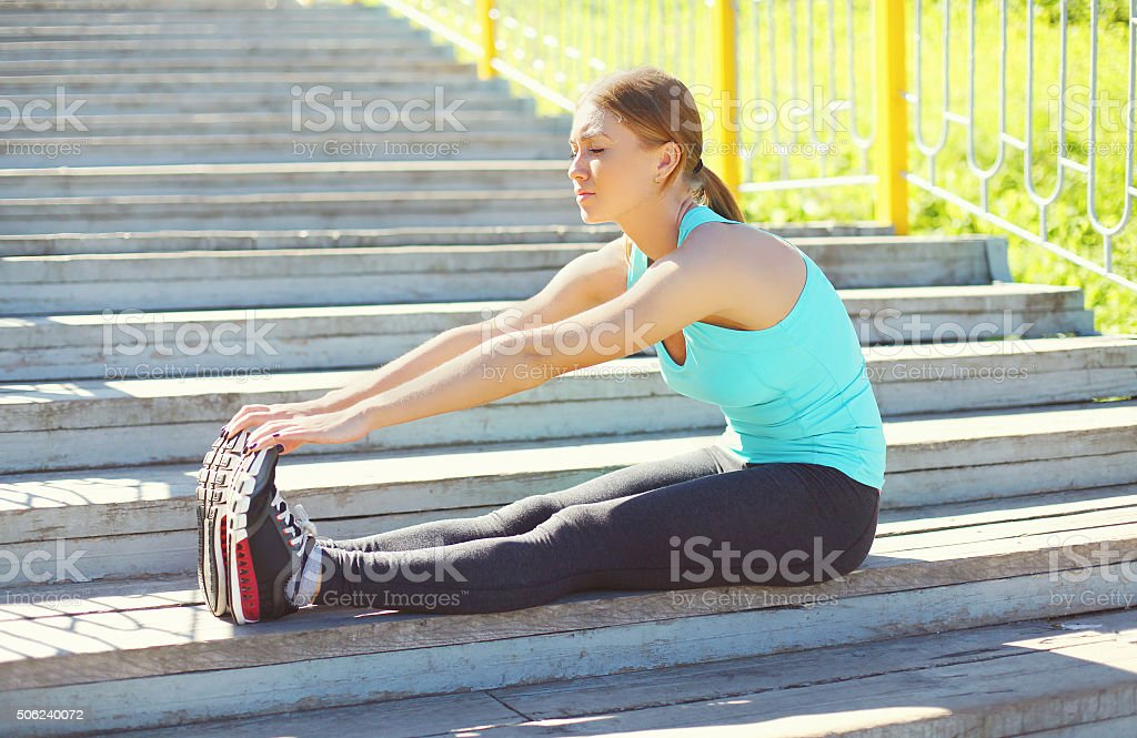 Sport, fitness concept - young woman doing stretching exercises stock photo