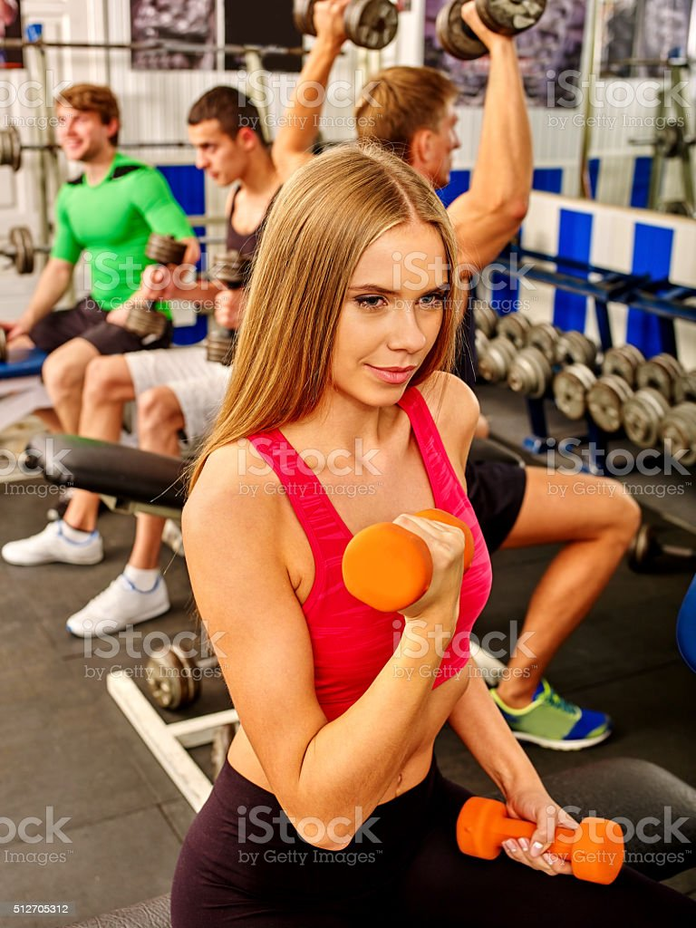 Sport girl in red holding dumbbells at sport gym. Biceps stock photo