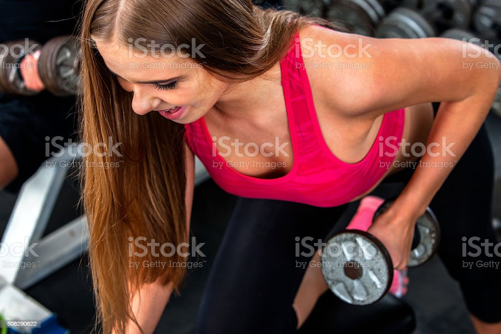 Sport girl wearing red holding dumbbells in sport gym. Biceps stock photo