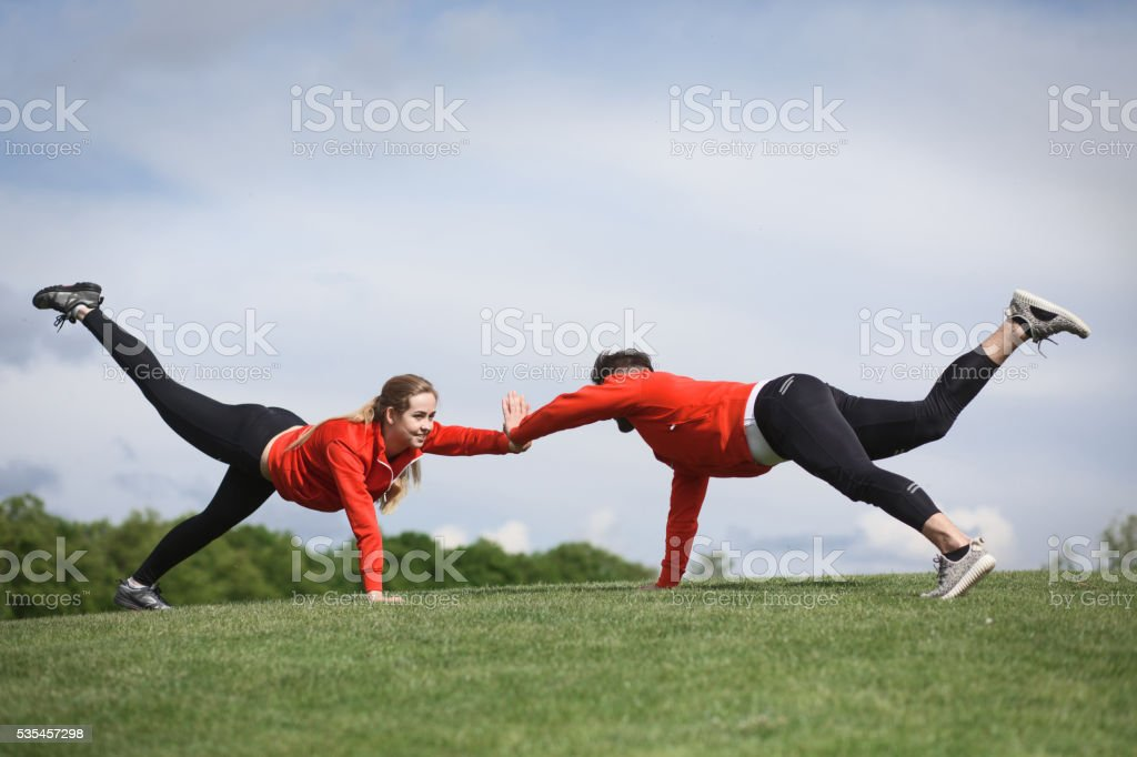 Sport man and woman in red jackets training in green park or forest....
