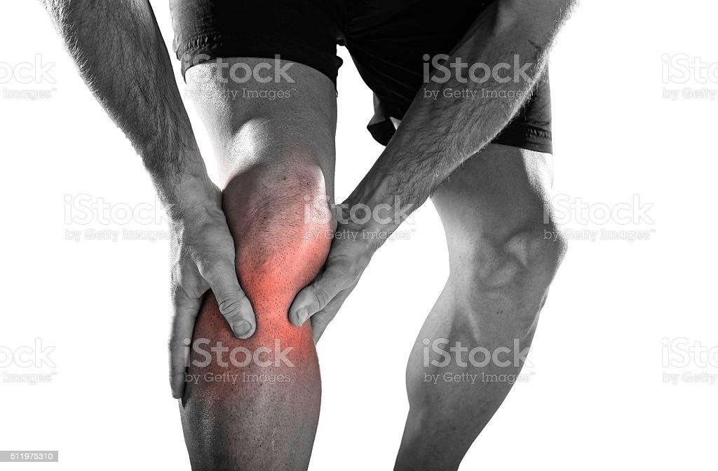 sport man holding knee with hands in pain running injury stock photo