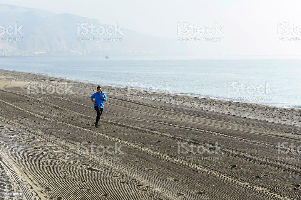 sport man running on desert beach in training workout stock photo