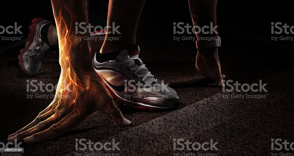 Sport. Runner. Hands on starting line. Fire and energy stock photo