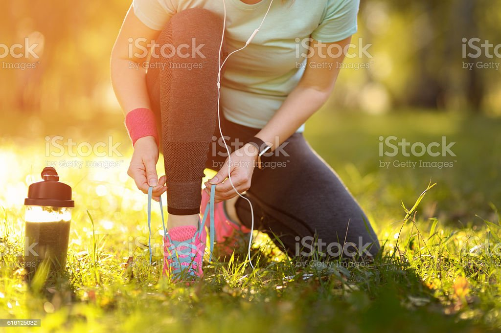Sport runner woman tying laces before training. Marathon. stock photo