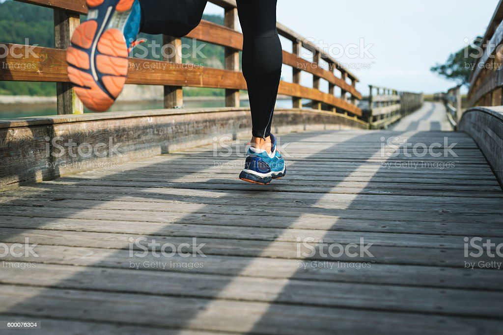 Sport running shoes closeup of man training outdoor on walkway stock photo