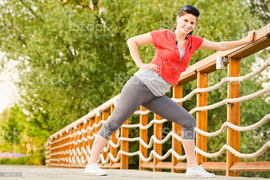 Sport series: cheerful woman stretching in the park stock photo