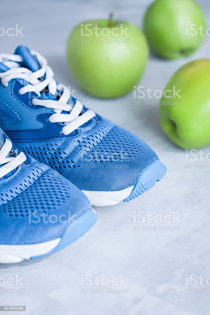 Sport shoes and apples on gray concrete background stock photo