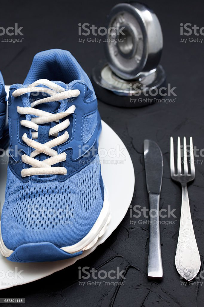 Sport shoes on wtite plate, fork and knife. stock photo