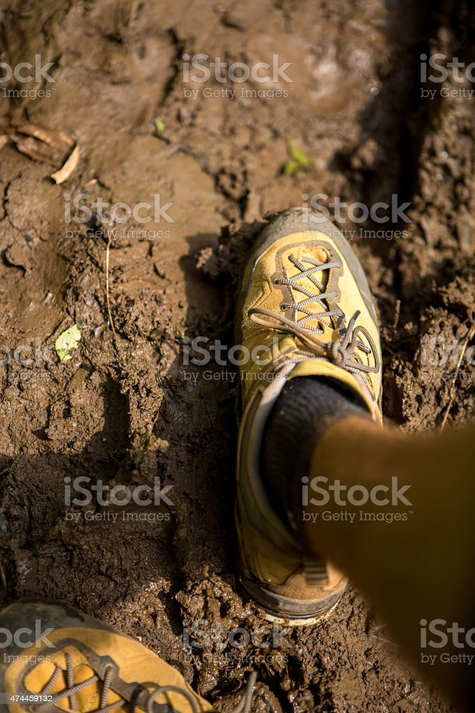 Sport shoes walking in mud ground stock photo