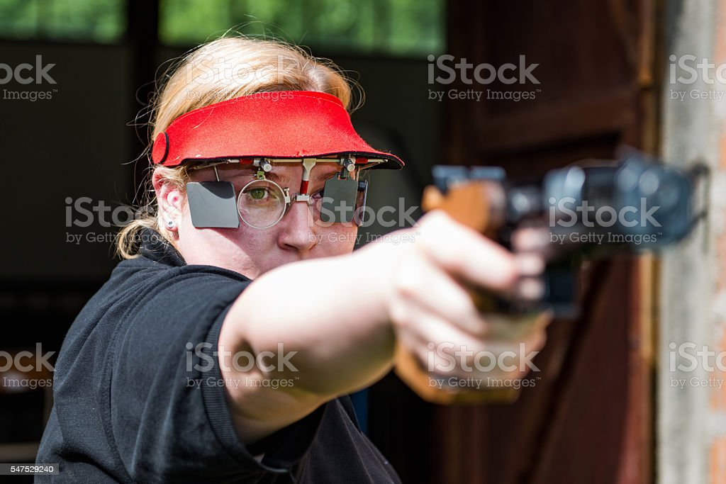 Sport shooting competitor aiming her gun stock photo