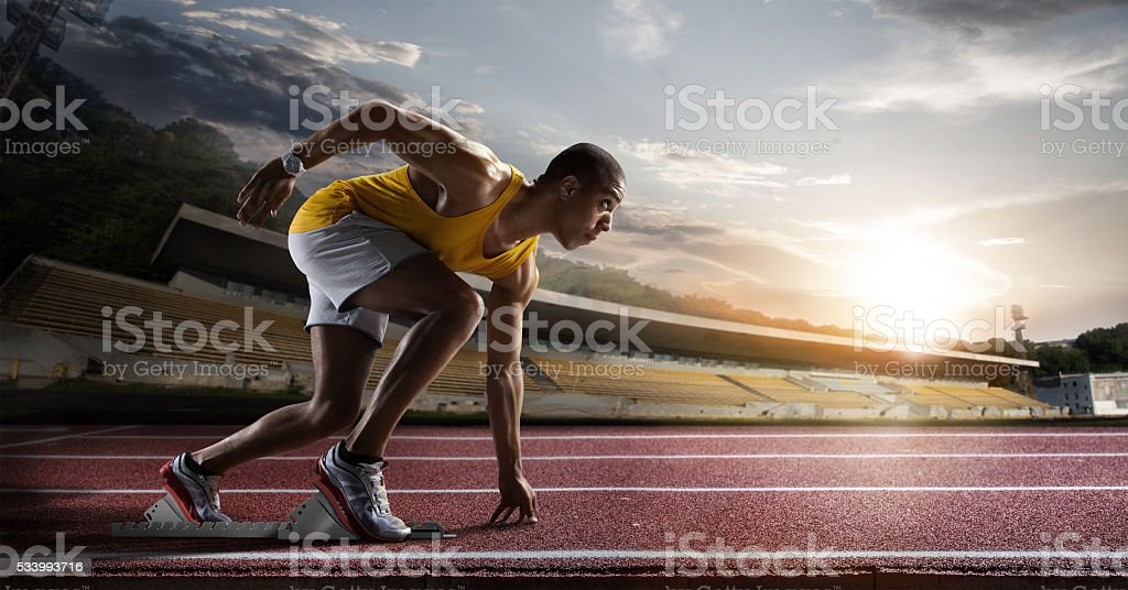 Sport. Sprinter leaving starting blocks on the running track. stock photo