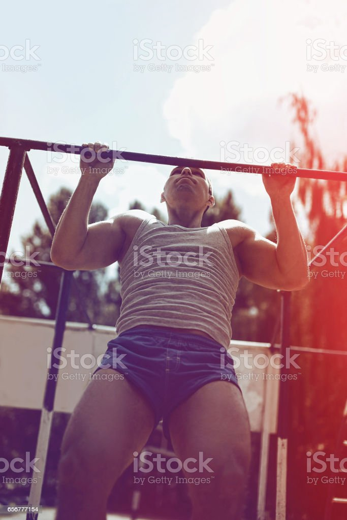 Sport, street workout, strength concept - athlete doing pull ups on...