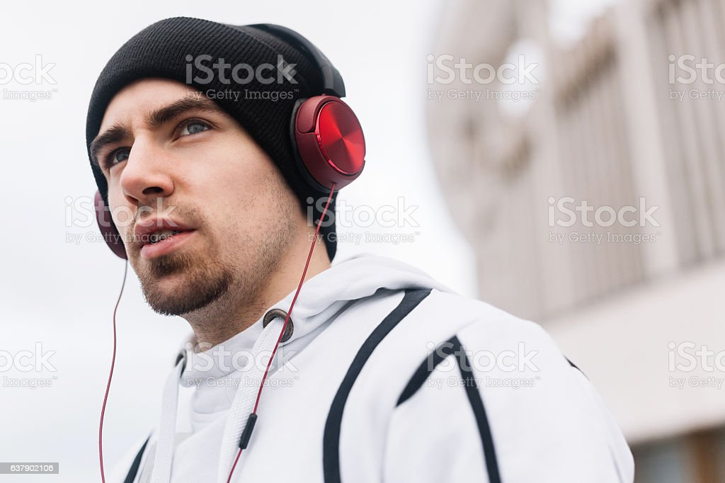 Attractive guy in sportswear listening to music during sport training