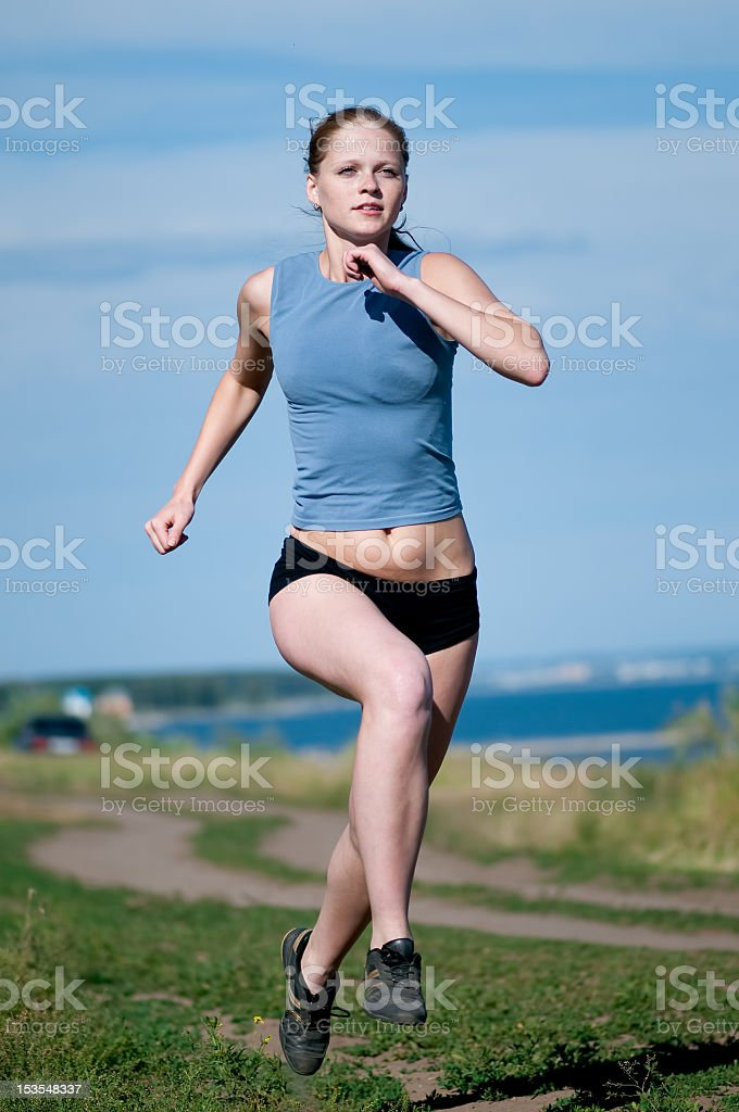 Sport teenage girl running over blue sky royalty-free stock photo