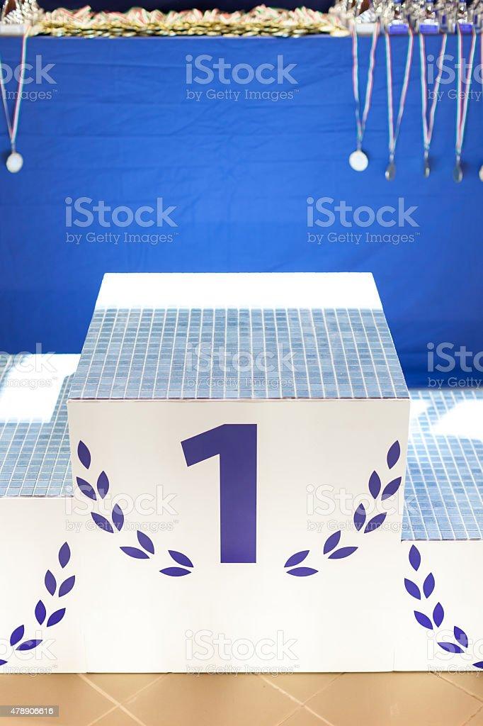 Sport winners pedestal with laurel wreath stock photo